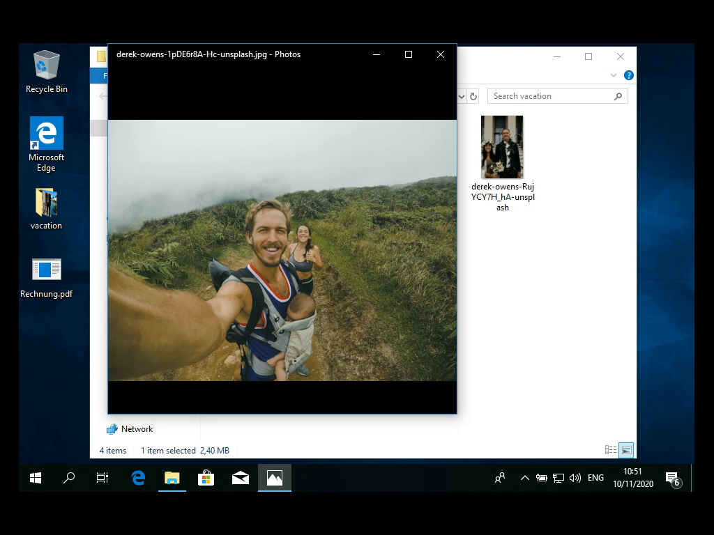 A screenshot of Windows 10 with a picture of a man doing a selfie in front of a woman.